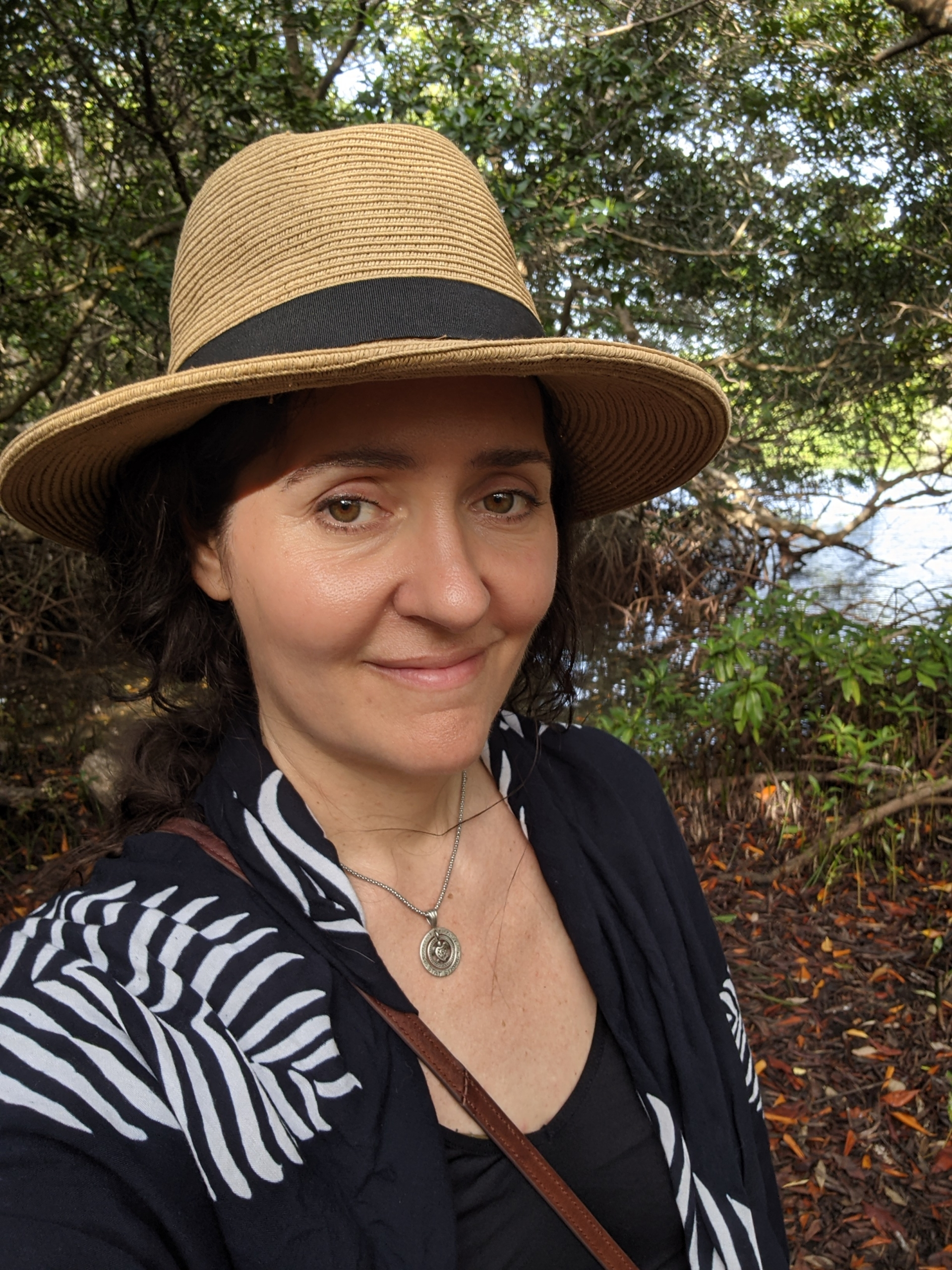 Lori Esposito smiling outside, with trees behind her. She is wearing a straw hat with a wide brim.